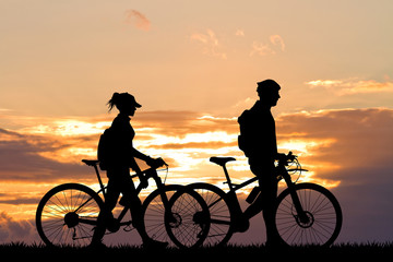 couple with bike at sunset