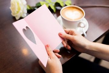close up of woman reading greeting card and coffee