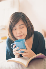 Young asian woman reading book and drinking coffee.