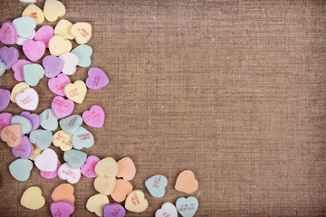 Candy conversation hearts on a brown background