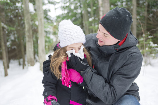 Father and daughter outdoor in the winter forest