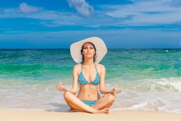 Young beautiful girl in bikini and straw white hat on the beach