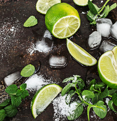 Fresh mint, slices of lime, ice, sugar over black metal surface . Top view.