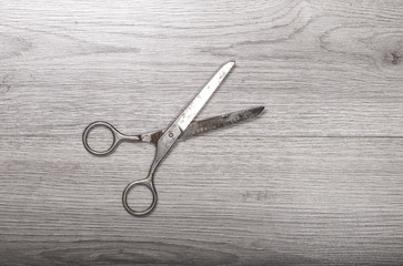 pair of scissors sits half open on a wood