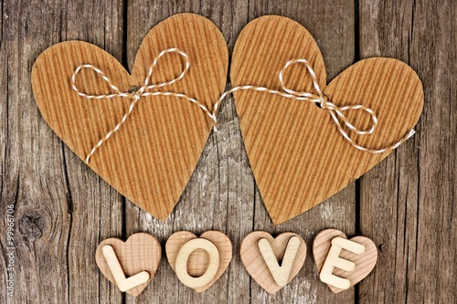 Rustic Heart Shaped Gift Tags With LOVE Wood Letters Against A Vintage Wooden Background