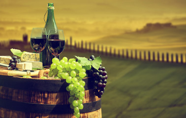 Wall Mural - Red wine bottle and wine glass on old barrel.