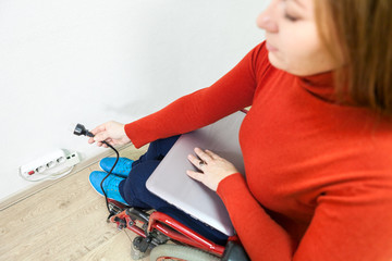Disabled Caucasian woman in wheelchair trying to insert laptop plug into power socket