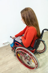 Disabled Caucasian woman sitting wheelchair and trying to insert laptop plug into power socket, fisheye lens