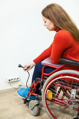 Disabled Caucasian woman has some issues while inserting power plug into outlet