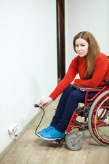 Paralyzed legs woman sitting wheelchair with power plug in hand, looking at camera and trying to insert laptop plug into power socket