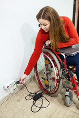 Smiling disabled woman sitting wheelchair with power plug in hand, stretching to power outlet in wall