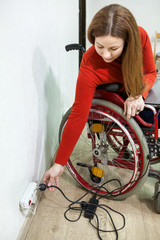 Young disabled woman sitting wheelchair with power plug in hand, stretching to power outlet in wall