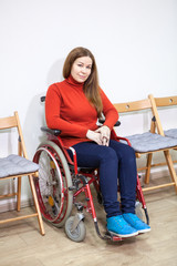 Positive smiling disabled woman in wheel-chair looking at camera while sitting between chairs indoor