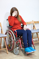 Disabled crying woman in wheel-chair covers her face with hand while sitting between chairs indoor