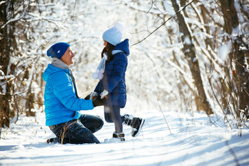 father and daughter playing in the snow in winter