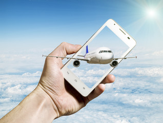 Airliner flying out of smartphone screen against cloudy landscap