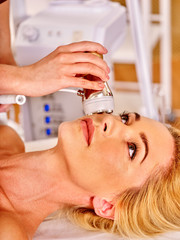 Woman receiving electric facial massage on microdermabrasion equipment .