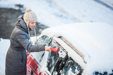 Young woman cleaning her car from snow and frost on a winter