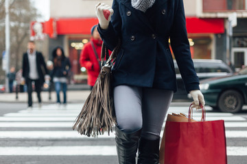 Closeup of woman crossing the street after shopping