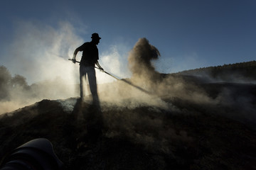Silhouette of coal man working at sunset in smoke