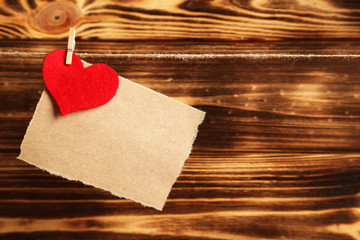 Blank paper hanging on rope on brown wooden background
