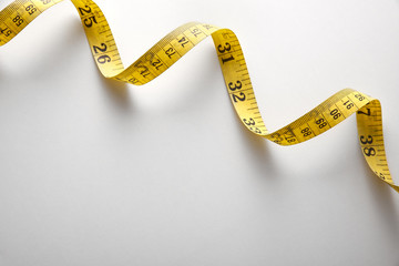 Yellow tape measure in meters and inches spiral and diagonal