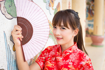 Beautiful Asian woman wearing traditional Cheongsam on chinese pattern traditional background