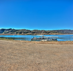 Wider view of Lake Casitas boats with low water line in background.