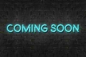 """COMING SOON"" neon sign shining on black brick wall,Business con"