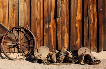 Old wild west  wooden barn with horse saddle and wagon wheel