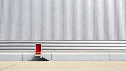 the sheet metal factory wall with the red door entrance