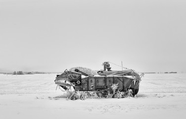 Vintage agricultural threshing machine in a black and white winter landscape