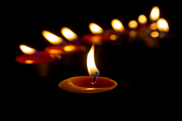 Fototapeta Burning candles on a dark background with warm light obraz