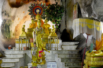 People praying with buddha statue inside cave at Wat Tham Khao Y
