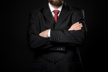 man dressed in strict suit folded arms. Black background