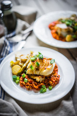 Roasted hake with romesco sauce and onion on wooden background