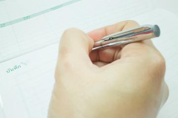 Hand on metallic pen write on the paper