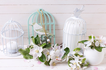 Apple blossom and candles in decorative bird cages