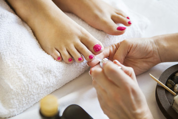 Woman in nail salon receiving pedicure by beautician