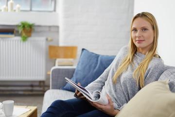 entspannte junge frau liest eine zeitung auf dem sofa