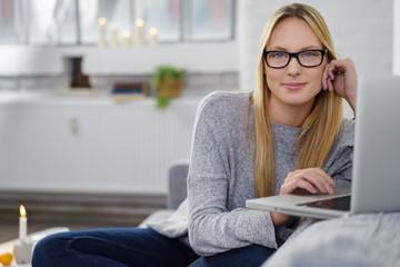 moderne junge frau mit laptop in ihrer gemütlichen wohnung