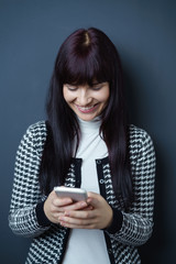 lachende frau liest nachrichten auf ihrem smartphone