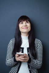 frau hält ihr smartphone in der hand und schaut lächelnd nach oben