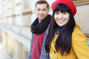 fröhliche junge frau mit ihrem freund unterwegs in der stadt