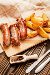 meat with vegetables , fried homemade sausage with roasted potatoes with garlic and pepper on a wooden background