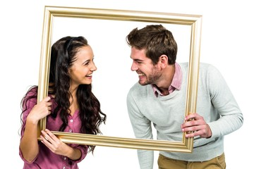 Stylish couple holding picture frame