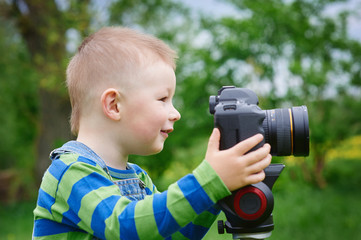 Little boy with an camera shooting outdoor
