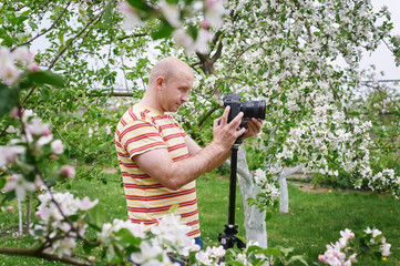 man shoot at the camera in a blossoming spring garden