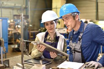 Metallurgy workers in workshop using digital tablet