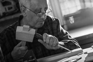 Senior carpenter working with a hammer and chisel in his workshop. Black and white.
